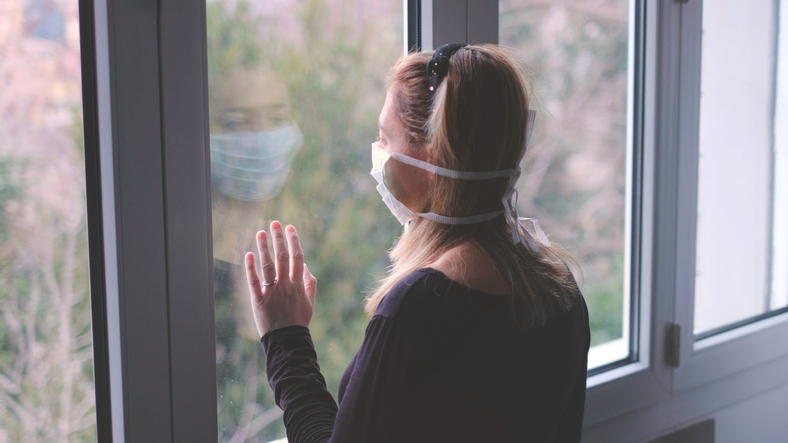 Woman looking out the window wearing a medical mask