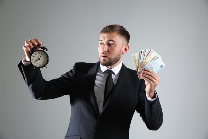 business man holding a clock and money