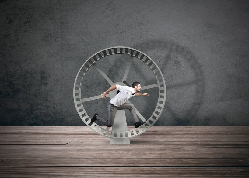 man running in a wheel getting no where and feeling overwhelmed.