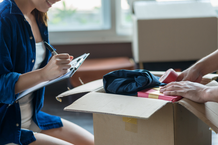 young couple packing and checking stuff using a checklist before moving to a new residence