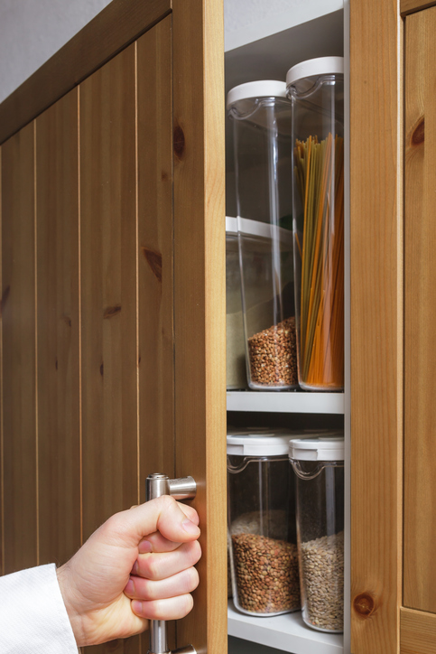 a person opening a pantry cupboard door