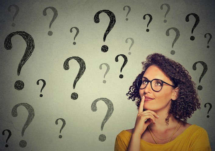 Thinking woman in glasses looking up at many question marks