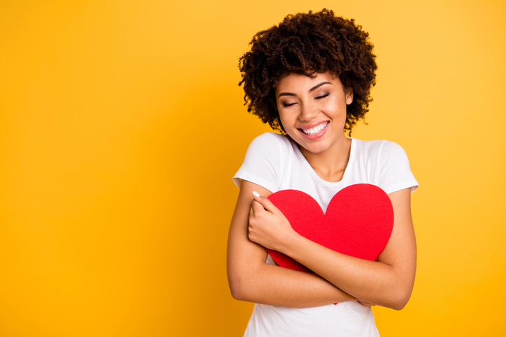 a beautiful woman hugging a pillow in the shape of a heart and smiling